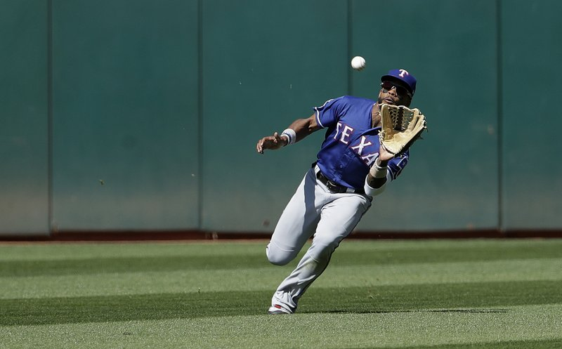 Texas Rangers center fielder Delino DeShields catches a fly ball hit by Oakland Athletics' Marcus Semien during the eighth inning of a baseball game in Oakland, Calif. (AP Photo/Jeff Chiu)
