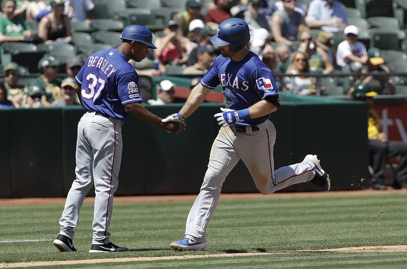 Texas Rangers' Logan Forsythe, right, is congratulated by third base coach Tony Beasley after hitting a solo home run against the Oakland Athletics during the fourth inning of a baseball game in Oakland, Calif. (AP Photo/Jeff Chiu)