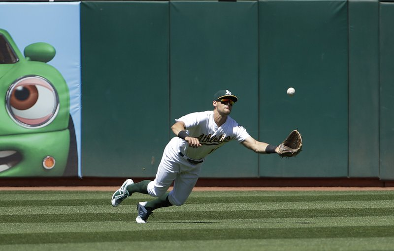 Oakland Athletics left fielder Chad Pinder catches a fly ball hit by Texas Rangers' Shin-Soo Choo during the fifth inning of a baseball game in Oakland, Calif. (AP Photo/Jeff Chiu)