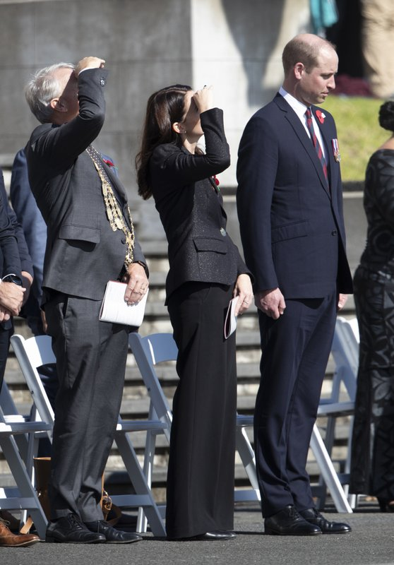 Britain's Prince William, right, stand with New Zealand Prime Minister Jacinda Ardern, center, after laying a wreath during an Anzac day service in Auckland, New Zealand, Thursday, April 25, 2019. (Brett Phibbs/SNPA via AP)