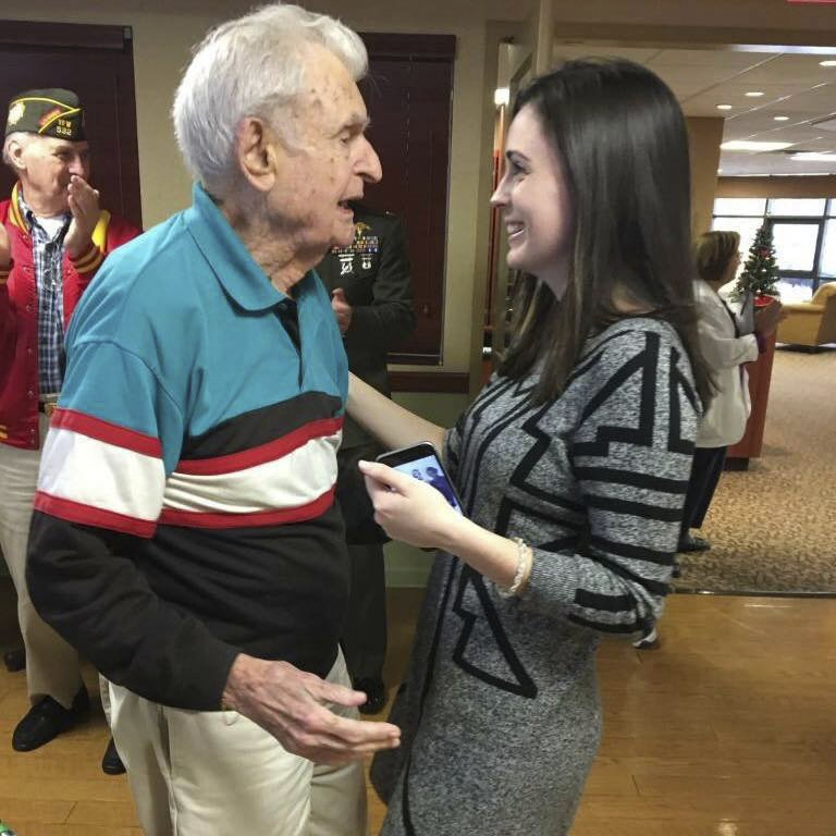In this December 2017 photo provided by Beth Regan, Regan speaks to Robert Graham in Cortland, N.Y. The decorated World War II veteran who died in April 2017 with no living relatives is being honored thanks to an unlikely friendship with the young woman who is determined to give him a farewell befitting a hero. (AP Photo/Jim Regan)