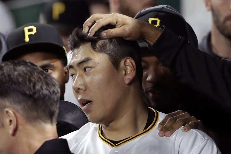 Pittsburgh Pirates' Jung Ho Kang, center, celebrates in the dugout after hitting a solo home run off Arizona Diamondbacks starting pitcher Merrill Kelly in the sixth inning of a baseball game in Pittsburgh, Wednesday, April 24, 2019. (AP Photo/Gene J. Puskar)