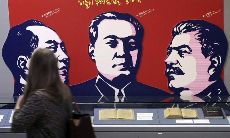 In this April 23, 2019 photo, a visitor looks at banner showing the late leaders, from left, of China's Mao Zedong, North Korea's Kim Il Song, Russia's Joseph Stalin as she tours the exhibition hall of the Korean War in Seoul, South Korea, Tuesday, April 23, 2019. (AP Photo/Lee Jin-man)