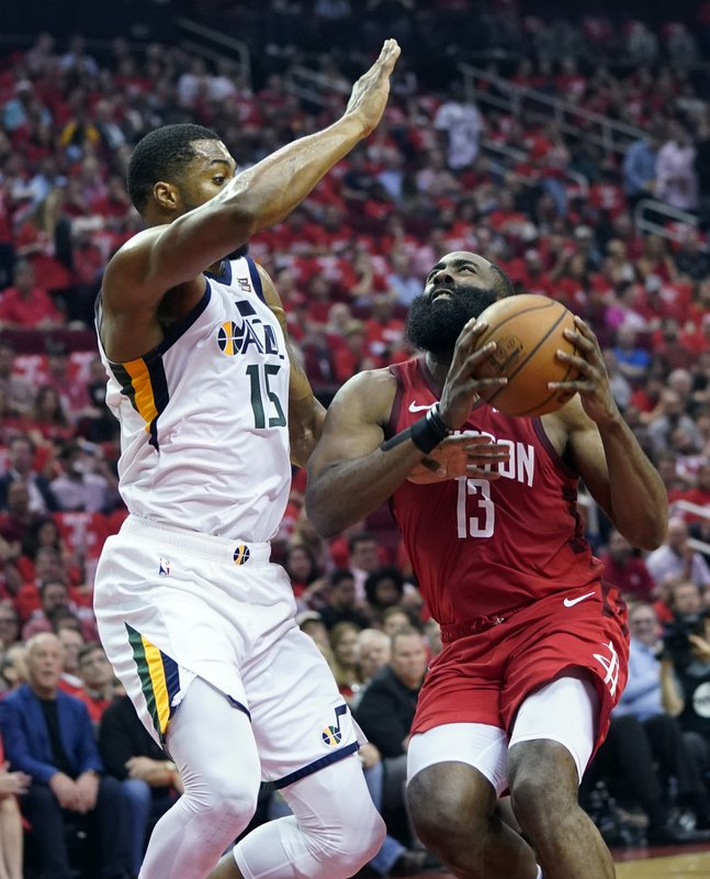 Houston Rockets guard James Harden (13) drives to the basket against Utah Jazz forward Derrick Favors (15) during the first half in Game 5 of an NBA basketball playoff series, in Houston, Wednesday, April 24, 2019. (AP Photo/David J. Phillip)