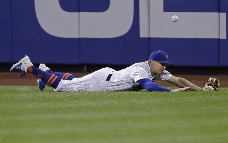 New York Mets' Brandon Nimmo dives for a ball hit by Philadelphia Phillies' Rhys Hoskins for a triple during the eighth inning of a baseball game, Wednesday, April 24, 2019, in New York. (AP Photo/Frank Franklin II)