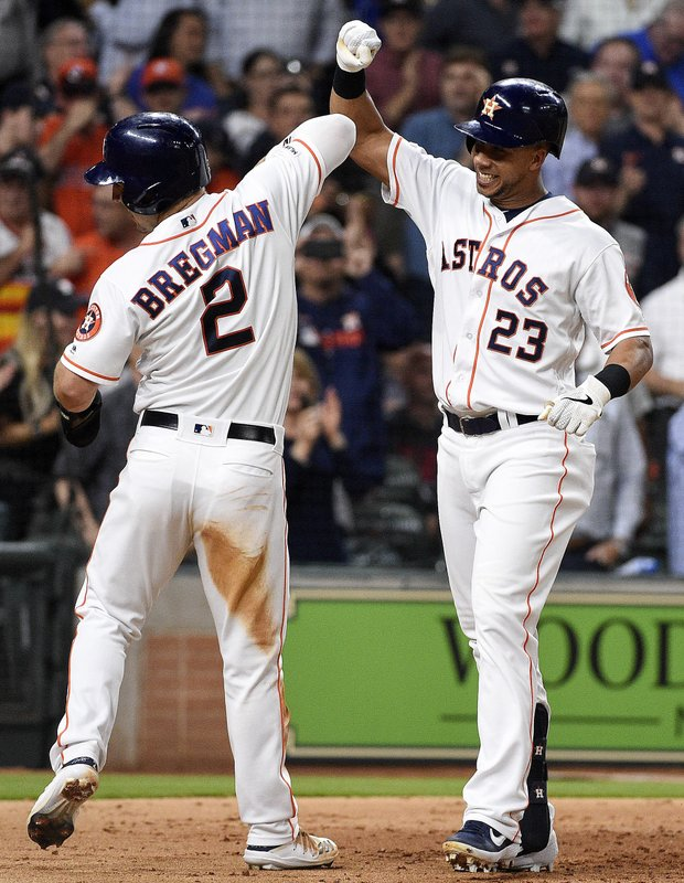 Houston Astros' Michael Brantley (23) celebrates his two-run home run off Minnesota Twins starting pitcher Kohl Stewart with Alex Bregman during the third inning of a baseball game, Wednesday, April 24, 2019, in Houston. (AP Photo/Eric Christian Smith)