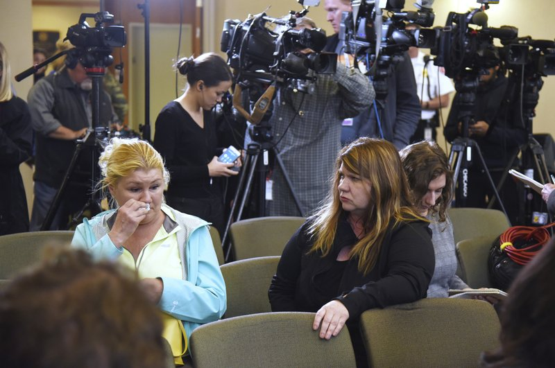 Long time Crystal Lake resident Danielle Hein, left, wipes away tears after sitting in a press conference at the Crystal Lake village hall where officials announced charges against the parents of Andrew