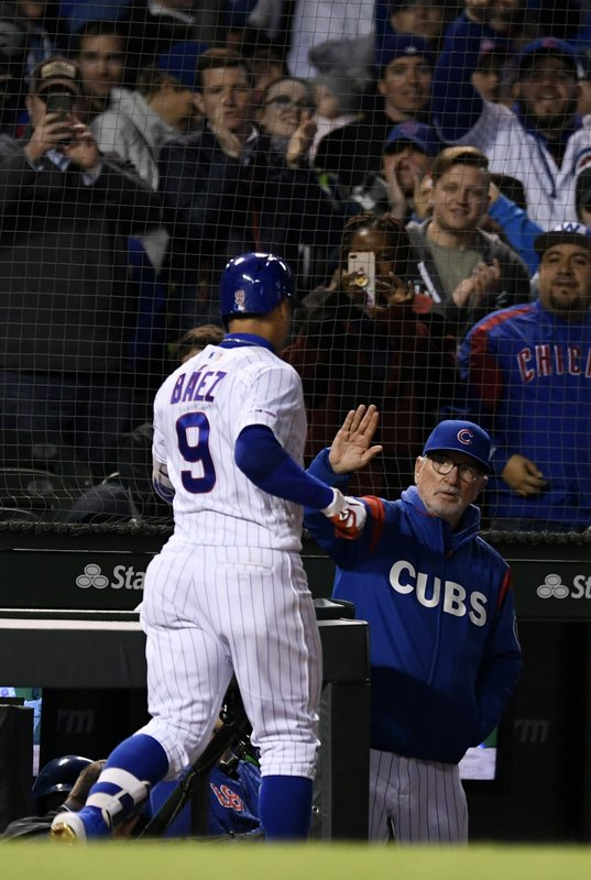 Chicago Cubs' Javier Baez (9) celebrates with manager Joe Maddon in the dugout after hitting a three-run home run during the sixth inning of a baseball game against the Los Angeles Dodgers, Wednesday, April 24, 2019, in Chicago. (AP Photo/Paul Beaty)