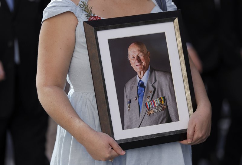 A woman carries a photo of a veteran during a march celebrating ANZAC Day, a national day of remembrance in Australia and New Zealand that commemorates those that served and died in all wars, conflicts, and while peacekeeping, in Sydney, Australia, Thursday, April 25, 2019. (AP Photo/Rick Rycroft)