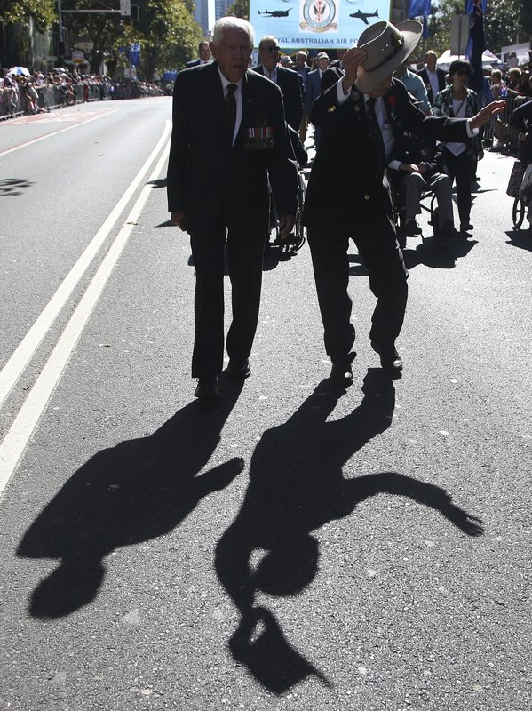 The shadow of an Australian veteran, right, is cast on the ground as he waves his hat during a march celebrating ANZAC Day, a national day of remembrance in Australia and New Zealand that commemorates those that served and died in all wars, conflicts, and while peacekeeping, in Sydney, Australia, Thursday, April 25, 2019. (AP Photo/Rick Rycroft)