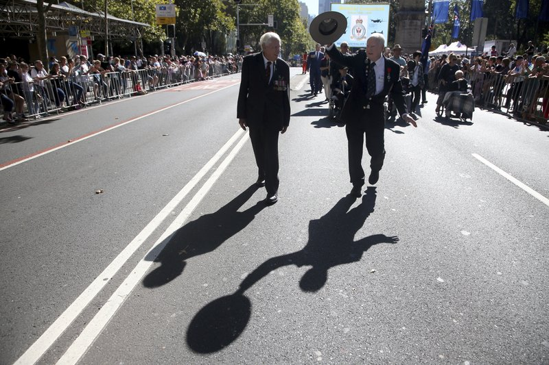 An Australian veteran, right, waves his hat during a march celebrating ANZAC Day, a national day of remembrance in Australia and New Zealand that commemorates those that served and died in all wars, conflicts, and while peacekeeping, in Sydney, Australia, Thursday, April 25, 2019. (AP Photo/Rick Rycroft)