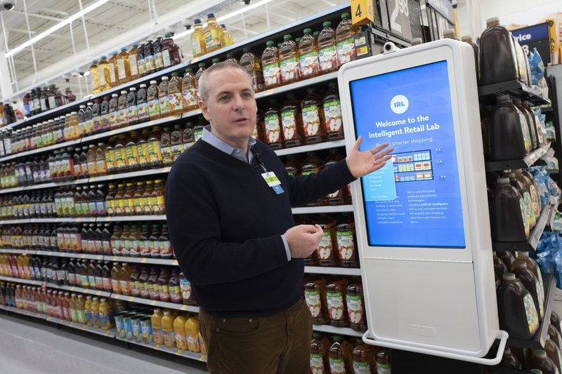 Mike Hanrahan, CEO of Walmart's Intelligent Retail Lab, discusses a kiosk that describes to customers the high technology in use at a Walmart Neighborhood Market, Wednesday, April 24, 2019, in Levittown, N. (AP Photo/Mark Lennihan)