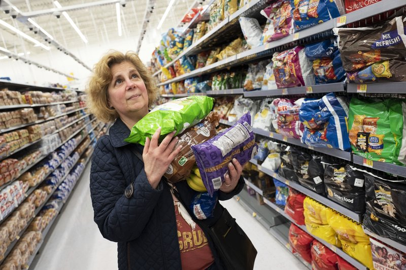 Marcy Seinberg shops at a Walmart Neighborhood Market, Wednesday, April 24, 2019, in Levittown, N.Y. Despite the signs and visible cameras many shoppers, including Seinberg, didn't seem to notice or care. (AP Photo/Mark Lennihan)