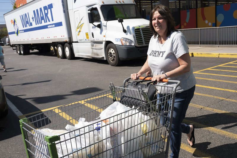 A customer pushes her cart into the parking lot after shopping at a Walmart Neighborhood Market, Wednesday, April 24, 2019, in Levittown, N. (AP Photo/Mark Lennihan)