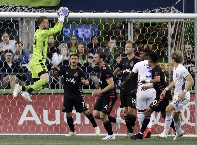 Seattle Sounders goalkeeper Stefan Frei, left, leaps to make a stop against the San Jose Earthquakes during the first half of an MLS soccer match, Wednesday, April 24, 2019, in Seattle. (AP Photo/Ted S. Warren)
