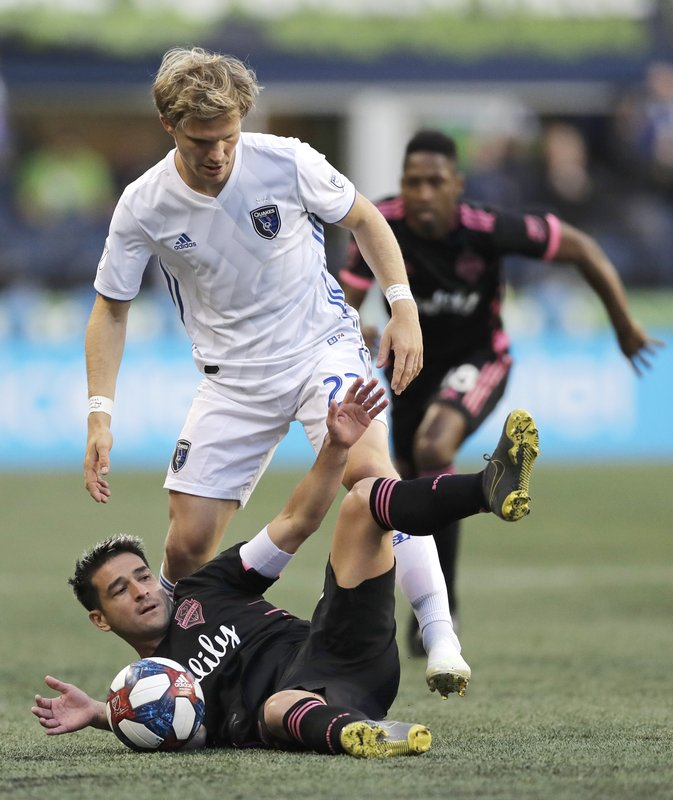 Seattle Sounders midfielder Nicolas Lodeiro, bottom, goes down next to San Jose Earthquakes defender Florian Jungwirth, standing, during the first half of an MLS soccer match, Wednesday, April 24, 2019, in Seattle. (AP Photo/Ted S. Warren)