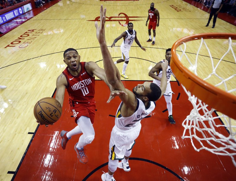 Houston Rockets guard Eric Gordon (10) drives to the basket past Utah Jazz center Rudy Gobert (27) during the second half of Game 5 of a first-round NBA basketball playoff series in Houston, Wednesday, April 24, 2019. (AP Photo/David J. Phillip)
