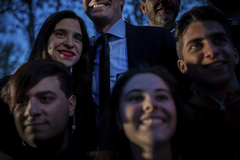 In this Tuesday, April 16, 2019 photo, Popular Party's candidate Pablo Casado, top and center, smiles while posing for snapshots with supporters after an election campaign event in Madrid, Spain. (AP Photo/Bernat Armangue)