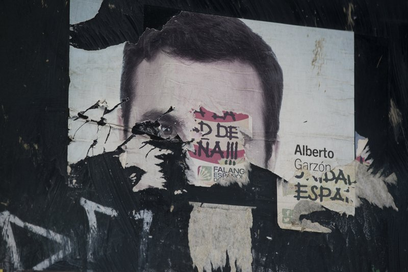 In this Tuesday April 23, 2019 photo, the torn remnants of election posters by Unidas/Podemos candidate for parliament Alberto Garzon and the right wing Falange party are seen on a wall in Madrid, Spain. (AP Photo/Paul White)
