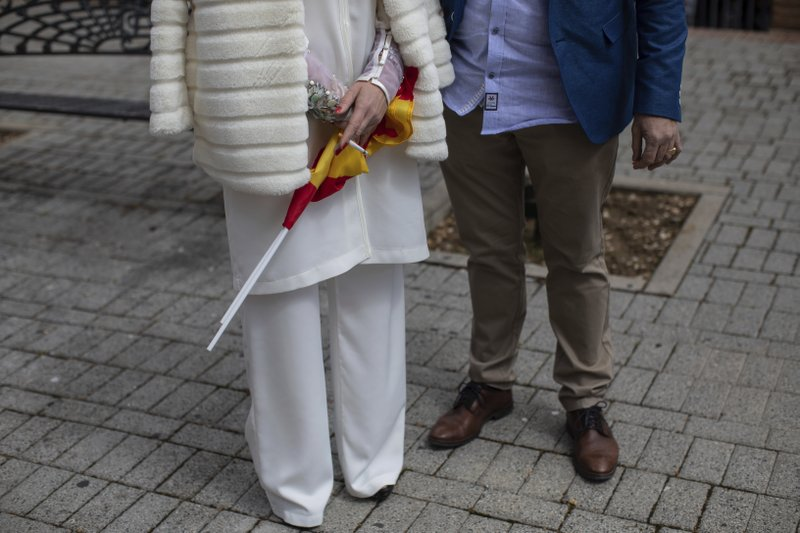 In this Saturday, April 6, 2019 photo, voters smoke a cigarette at the end of an event hosted by Spain's far-right Vox Party in Leganes, on the outskirts of Madrid, Spain. (AP Photo/Bernat Armangue)