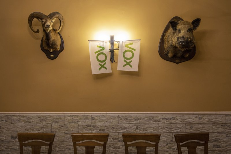 In this April 10, 2019 photo, Vox banners hang from a bar in Brazatortas, on the edge of the Alcudia valley, central Spain. (AP Photo/Bernat Armangue)