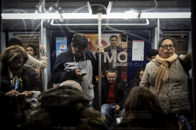 In this Wednesday, April 24, 2019 photo, a banner of Spanish election runner Citizens party's Albert Rivera is seen in the background in a subway station, in Madrid, Spain. (AP Photo/Bernat Armangue)