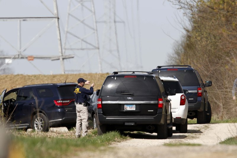 McHenry County Sheriff's officer search the area of Route 176 and Dean Street south of Woodstock, Ill. (Brian Hill/Daily Herald via AP)