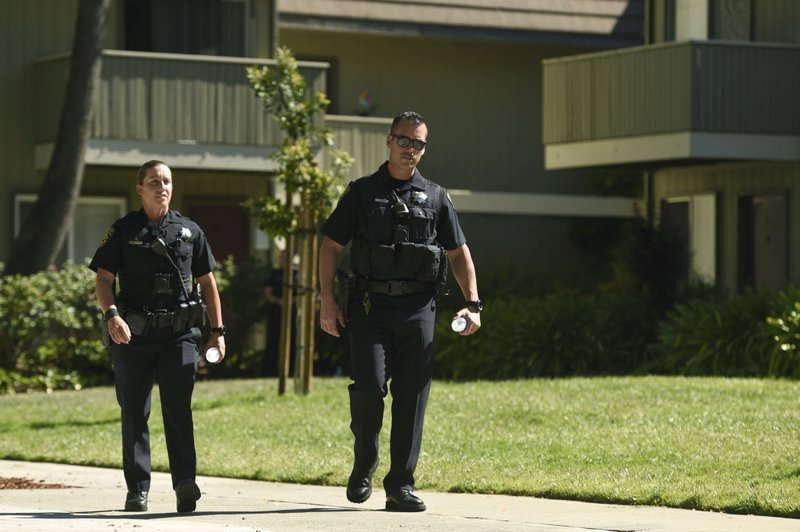Police stand outside an apartment complex believed to be associated with a car crash suspect in Sunnyvale, Calif. (AP Photo/Cody Glenn)