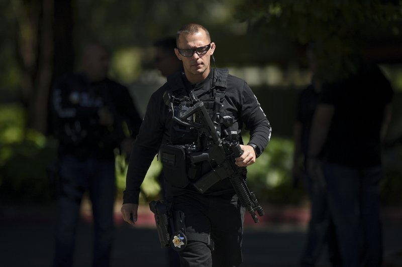 Police approach the apartment complex believed to be associated with a car crash suspect in Sunnyvale, Calif. (AP Photo/Cody Glenn)