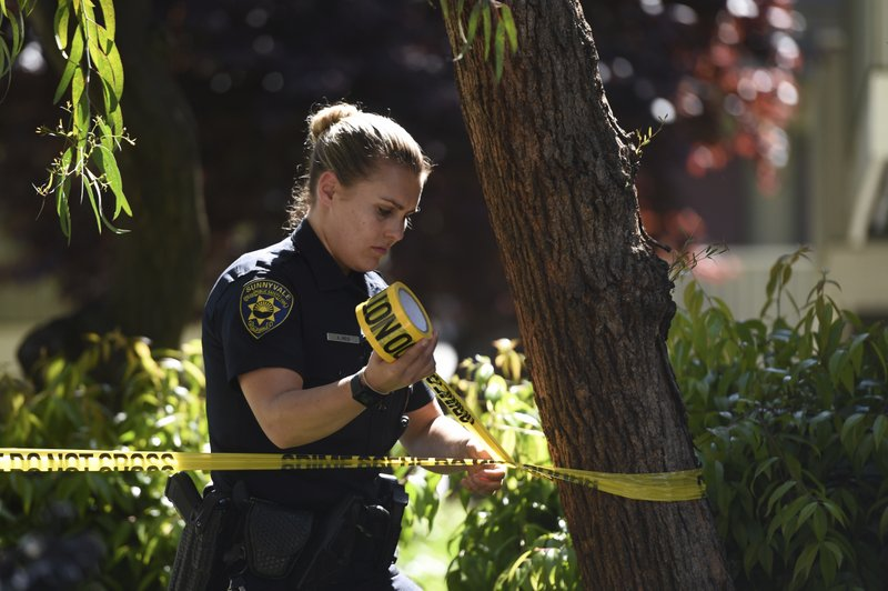 Sunnyvale Public Safety Officer Kira Reid secures the perimeter at the apartment complex believed to be associated with a car crash suspect in Sunnyvale, Calif. (AP Photo/Cody Glenn)