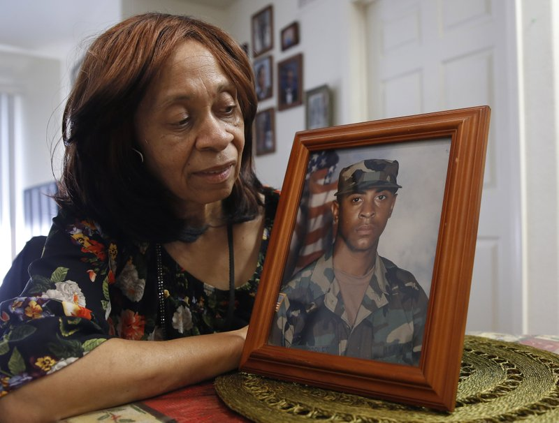 Leevell Peoples glances at a photo of her son, Isaiah Peoples, taken while he was in the Army, at her home Wednesday, April 24, 2019, in Sacramento, Calif. (AP Photo/Rich Pedroncelli)