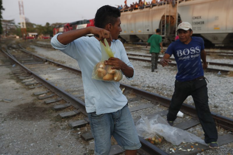 A Central American migrant holds his bag of bread away from another migrant, who attempts to take it away from him, before climbing on a north-bound freight train during his journey toward the US-Mexico border, in Ixtepec, Oaxaca state, Mexico, Tuesday, April 23, 2019. (AP Photo/Moises Castillo)