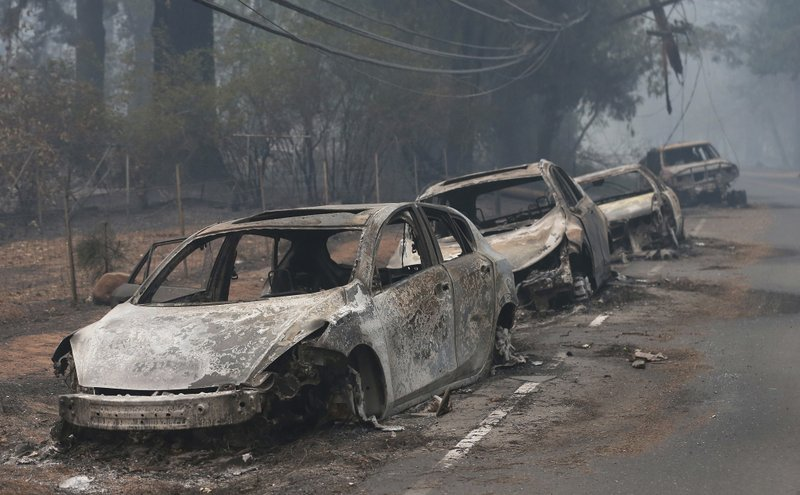 FILE - This Nov. 9, 2018, file photo the burned out hulks of cars abandoned by their drivers sit along a road in Paradise, Calif. (AP Photo/Rich Pedroncelli, File)