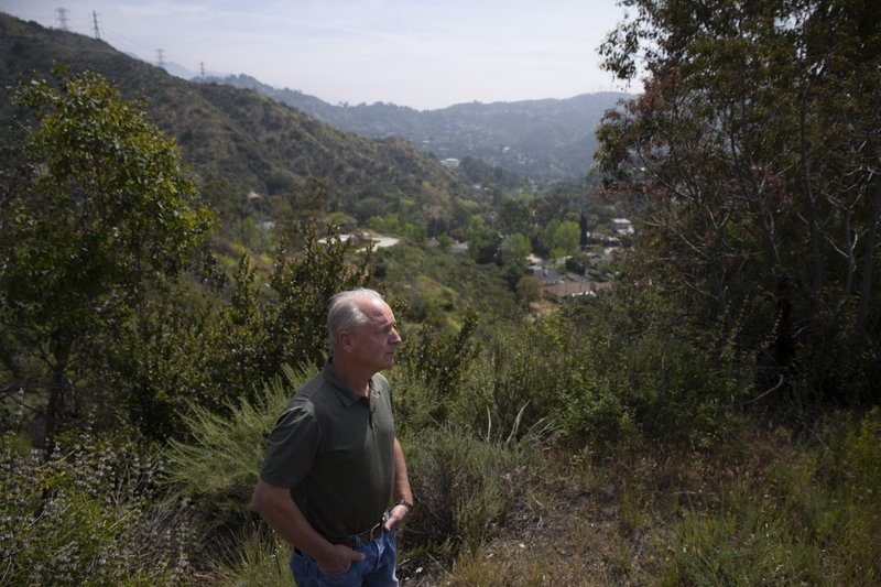 In this April 15, 2019 photo, Glendale, Calif., resident James Ward, 62, pauses for photos on a hilltop overlooking the Chevy Chase Canyon neighborhood of Glendale, Calif. (AP Photo/Jae C. Hong)