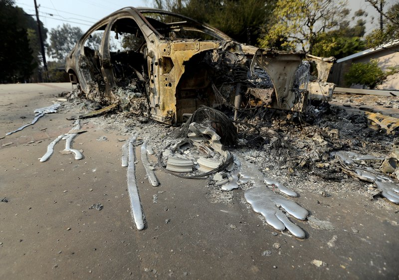 FILE - This Nov. 10 2018, file photo shows molten aluminum that flowed from a car that burned in front of one of at least 20 homes destroyed just on Windermere Drive in the Point Dume area of Malibu, Calif., (AP Photo/Reed Saxon, File)