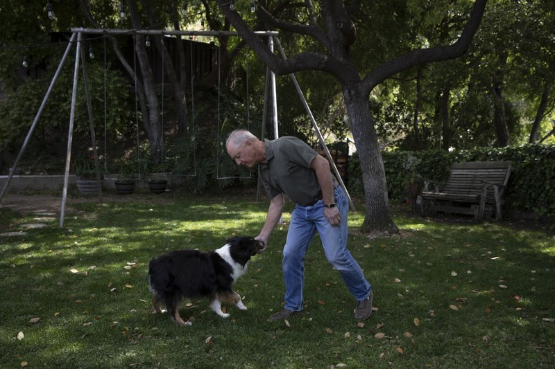 In this April 15, 2019 photo, James Ward, a 62-year-old Glendale, Calif., resident, plays with his dog in the backyard of his home in the Chevy Chase Canyon neighborhood of Glendale, Calif. (AP Photo/Jae C. Hong)
