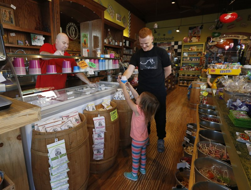 In this April 17, 2019, photo, Ricky Gregg buys a cup of ice cream for his daughter Kallie, 3, from Steve Leonte, in Sonora, Calif. (AP Photo/Rich Pedroncelli)