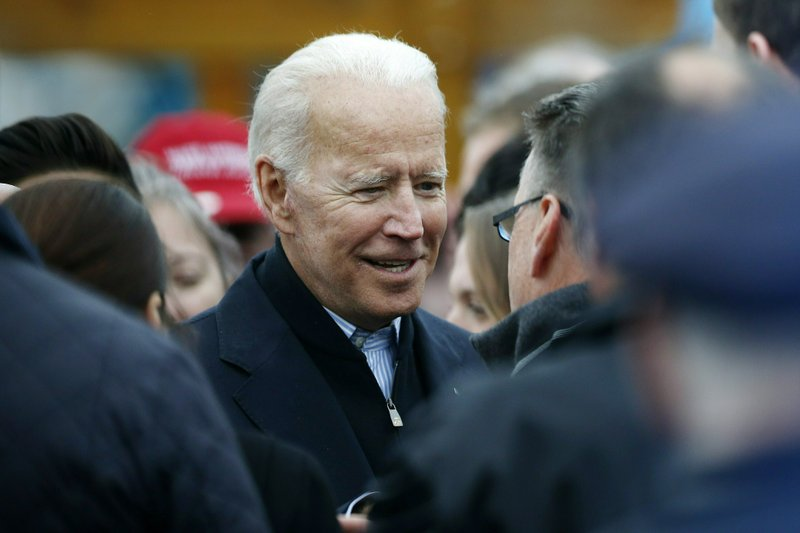 FILE - In this April 18, 2019, file photo, former vice president Joe Biden talks with officials after speaking at a rally in support of striking Stop & Shop workers in Boston. (AP Photo/Michael Dwyer, File)