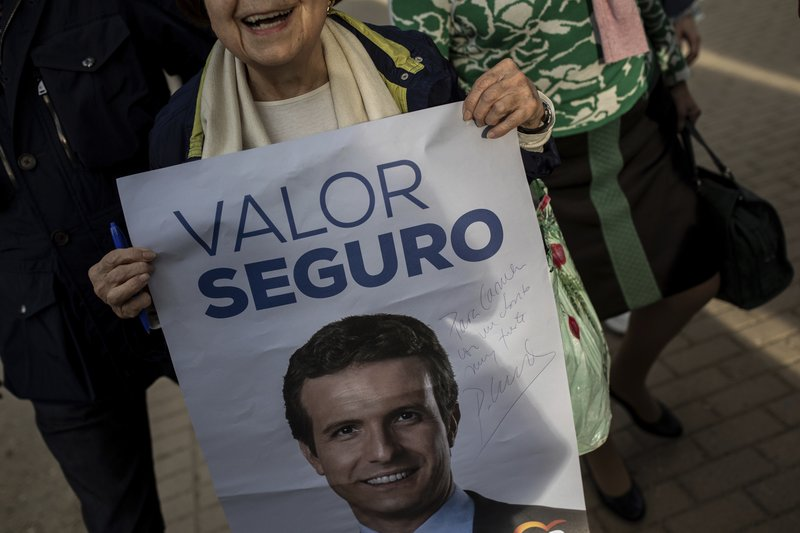 In this Tuesday, April 16, 2019 photo, a Spanish woman holds a poster signed by Popular Party's candidate Pablo Casado, during an election campaign event in Madrid, Spain. (AP Photo/Bernat Armangue)