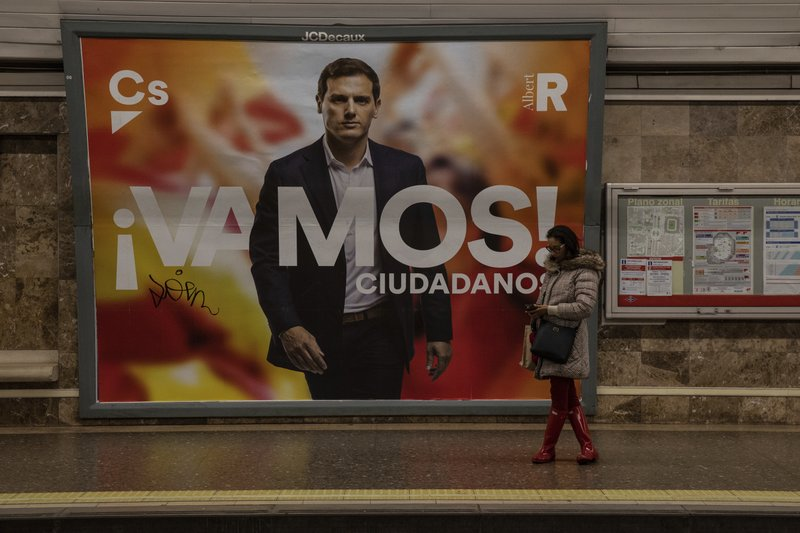 In this Wednesday, April 24, 2019 photo, a banner of Spanish election runner Citizens party's Albert Rivera is seen in the background in a subway station Madrid, Spain. (AP Photo/Bernat Armangue)