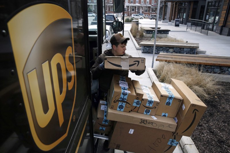 FILE- In this Dec. 19, 2018, file photo a UPS driver prepares to deliver packages. United Parcel Service Inc. (AP Photo/Patrick Semansky, File)