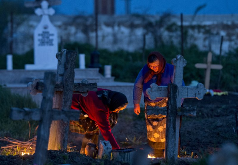 Women light fires by their relative's graves at dawn in Copaciu, southern Romania, Thursday, April 25, 2019. (AP Photo/Andreea Alexandru)