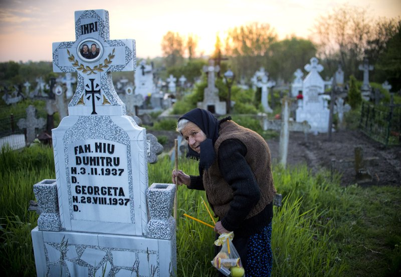 An elderly woman walks to a relative's grave at dawn in Copaciu, southern Romania, Thursday, April 25, 2019. (AP Photo/Andreea Alexandru)