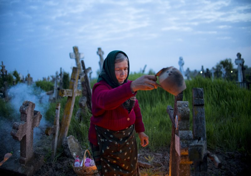 A woman spreads incense next to a relative's grave at dawn in Copaciu, southern Romania, Thursday, April 25, 2019. (AP Photo/Andreea Alexandru)