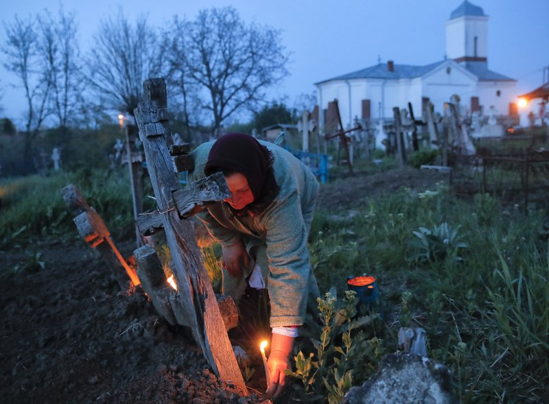 A woman lights a candle by a relative's grave at dawn in Copaciu, southern Romania, Thursday, April 25, 2019. (AP Photo/Vadim Ghirda)