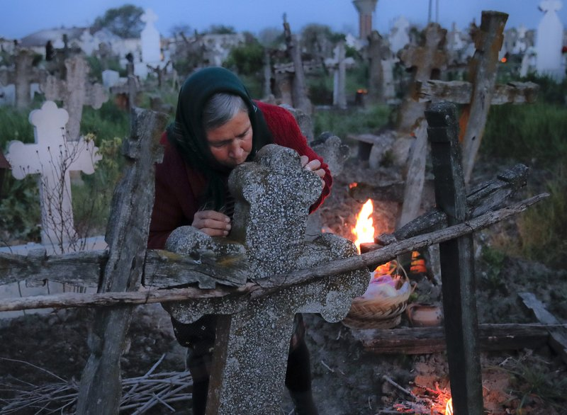 A woman kisses the cross of a relative's grave at dawn in Copaciu, southern Romania, Thursday, April 25, 2019. (AP Photo/Vadim Ghirda)