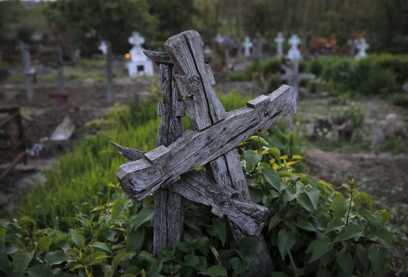Old wooden crosses intertwine in a cemetery at dawn in Copaciu, southern Romania, Thursday, April 25, 2019. (AP Photo/Vadim Ghirda)