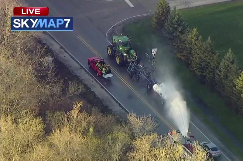 In this still image from video provided by ABC7 Chicago, a fire engine sprays water on a container of the chemical that farmers use for soil after after anhydrous ammonia leaked Thursday, April 25, 2019, in Beach Park, Ill. (ABC7 Chicago via AP)