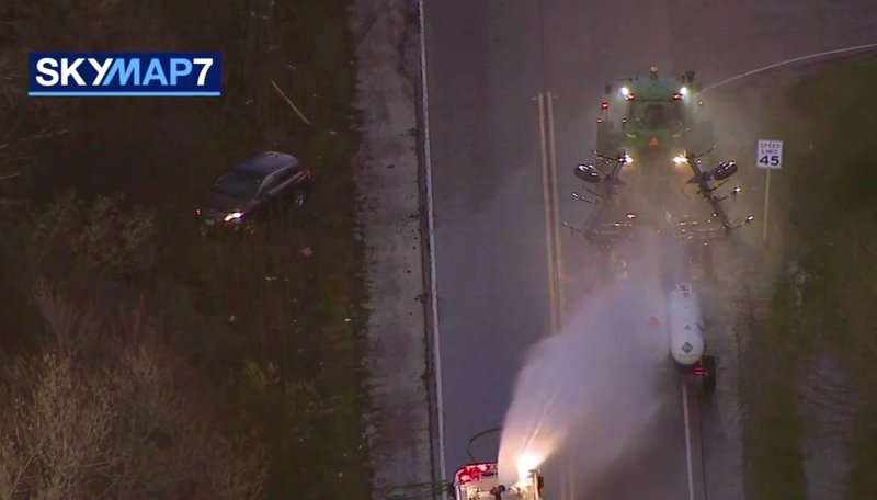 In this image made from video provided by ABC7 Chicago, a fire engine sprays water on a container of a chemical that farmers use for soil after anhydrous ammonia leaked Thursday, April 25, 2019, in Beach Park, Ill. (ABC7 Chicago via AP)