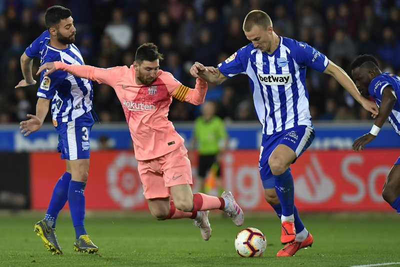 Barcelona forward Lionel Messi fights for the ball against Deportivo Alaves Rodrigo Ely during a Spanish La Liga soccer match between Deportivo Alaves and FC Barcelona at the Medizorrosa stadium in Vitoria, Spain, Tuesday, April 23, 2019. (AP Photo/Alvaro Barrientos)